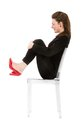 Woman sitting in lateral view expression white background Stock Photo