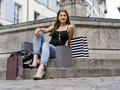 Woman sitting after long day shopping photo of a beautiful young with her bags at a fountain in an old european city resting Royalty Free Stock Image