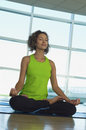 Woman sitting in lotus position at gym full length of young Royalty Free Stock Photography