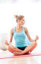 Woman sitting in lotus position working out at a health club Stock Photo