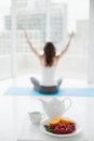 Woman sitting in meditation posture with healthy food in foreground blurred toned young at fitness studio Royalty Free Stock Photo