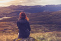 Woman sitting on mountain top and contemplating young is a rock a admiring the sunset Royalty Free Stock Photography