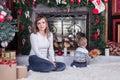 Woman sitting near a Christmas tree