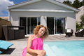 Woman sitting near the pool. woman wearing a pink dress Royalty Free Stock Photo