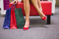 Woman sitting next to shopping bags and putting on shoes Royalty Free Stock Photo