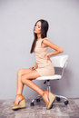Woman sitting on office chair with backpain