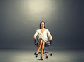 Woman sitting on the office chair smiley young businesswoman over dark background Royalty Free Stock Photos