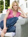 Woman sitting outdoors on patio smiling Royalty Free Stock Image