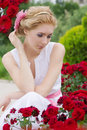 Woman sitting among pink rose garden sensual Stock Images