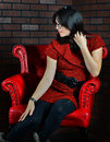 Woman sitting in red chair a beautiful young sits a as she runs her fingers through her hair with one hand and caresses her leg Royalty Free Stock Photos