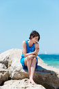 Woman sitting on rocks at the seaside pretty young in a blue summer dress watching rythmic motion of ocean surf Royalty Free Stock Photos