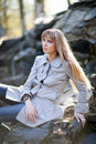 Woman sitting on the rocks young beautiful in a gray coat Stock Photos