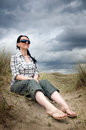 Woman sitting in sand dunes Stock Photo