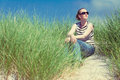 Woman sitting in sand dunes amongst tall grass relaxing, enjoying the view on sunny day