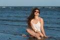 Woman sitting in sea water wear bikini, sunglasses and white shirt Royalty Free Stock Photo