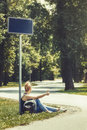 Woman sitting on a side of the road under the street sign, surrounded by trees, hitchhiking Royalty Free Stock Photo