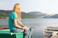Woman sitting on small boat looking at lake Royalty Free Stock Photo