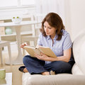 Woman sitting on sofa enjoying reading book Stock Photography