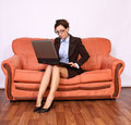 Woman sitting on the sofa working on  lap top Stock Photo