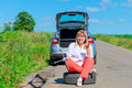 Woman sitting on the spare wheel with the tools road Stock Photo