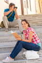 Woman sitting on stairs reading man photographing Stock Images