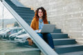 Woman sitting on stairs while using laptop young red haired looking away Stock Photography