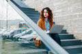 Woman sitting on stairs while using laptop young red haired looking away Royalty Free Stock Image