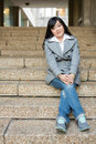 Woman sitting on stairs young asian in in front of a business building Stock Image