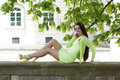 Woman sitting on stone wall smiling under a tree Stock Photography