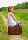 Woman sitting on suitcase Stock Images