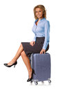 Woman sitting on suitcase attractive flight attendant is a blue studio shot of a beautiful smiling down a Royalty Free Stock Photos