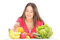 Woman sitting at table with fruits and vegetables isolated on white background Royalty Free Stock Photo