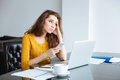 Woman sitting at the table with laptop and smartphone sad home Royalty Free Stock Photos