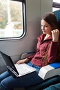 Woman is sitting in the train with laptop Stock Images