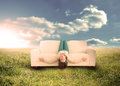 Woman sitting upside down on couch in field silly sunny countryside Royalty Free Stock Photos