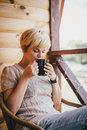 Woman sitting in a wicker chair on a balcony with a cup of tea pretty young knitted sweater cozy hot or coffee or cocoa Royalty Free Stock Images