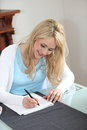 Woman sitting writing at home smiling young blond in a notepad seated her dining room table Stock Images
