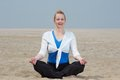 Woman sitting in yoga position at the beach mature Royalty Free Stock Photography