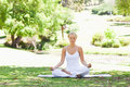 Woman sitting in a yoga position on the lawn Stock Photos