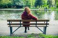 Woman sittng on bench by a pond in the park Royalty Free Stock Photo