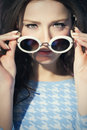 Woman sixties style closeup of a young in retro with old fashioned sunglasses under bright spotlight Stock Photos