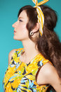 Woman sixties style fashion in colorful summer dress with retro hairstyle and makeup posing over cyan blue background Stock Photography