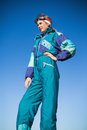 Woman in ski suit with one hand on hip looking away blue sky behind Stock Photos