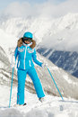 Woman in ski suit stands on background of mountain Stock Images