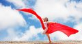 Woman on sky background with red tissue Royalty Free Stock Photo