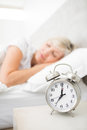 Woman sleeping in bed with alarm clock in foreground at bedroom blurred mature Royalty Free Stock Image