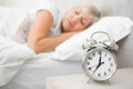 Woman sleeping in bed with alarm clock in foreground at bedroom blurred mature Stock Image