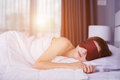 Woman sleeping on bed with eye mask in bedroom with soft light Royalty Free Stock Photo