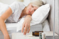 Woman sleeping in bed with pills in foreground closeup of a mature at home Stock Images