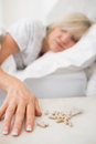 Woman sleeping in bed with pills in foreground closeup of a mature at home Stock Image